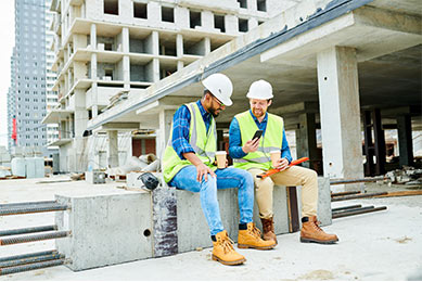Two Construction Workers Using Mobile Device to Sell Hotel Reservations